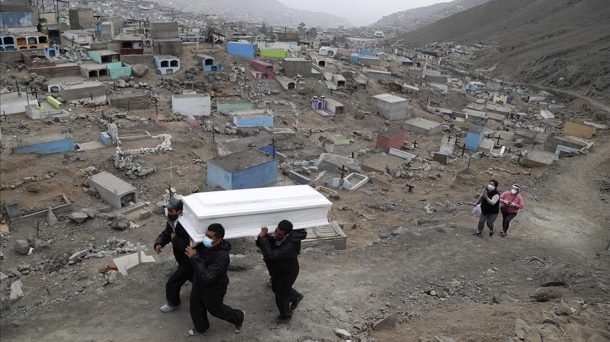 Trabajadores de un cementerio de Lima portan el féretro de un fallecido por covid, el miércoles pasado.