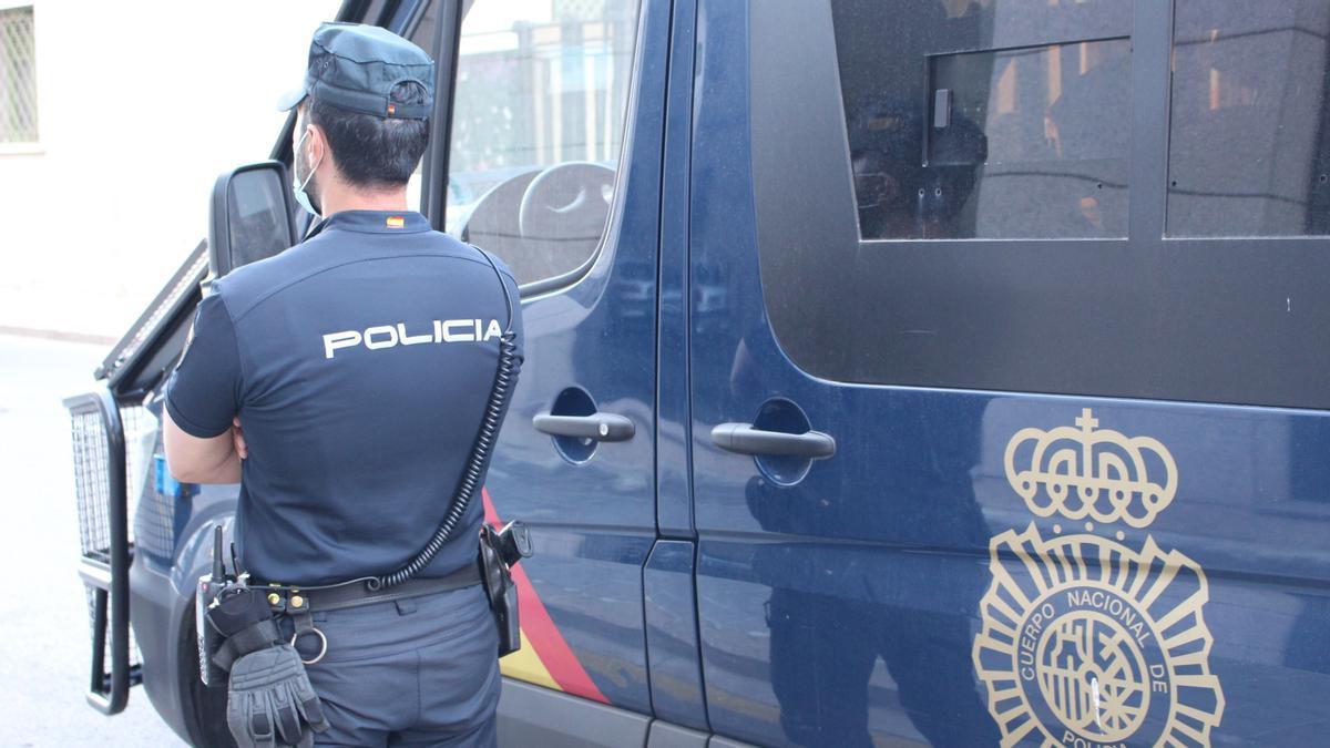Agente de la Policía Nacional junto al vehículo policial en Valencia.