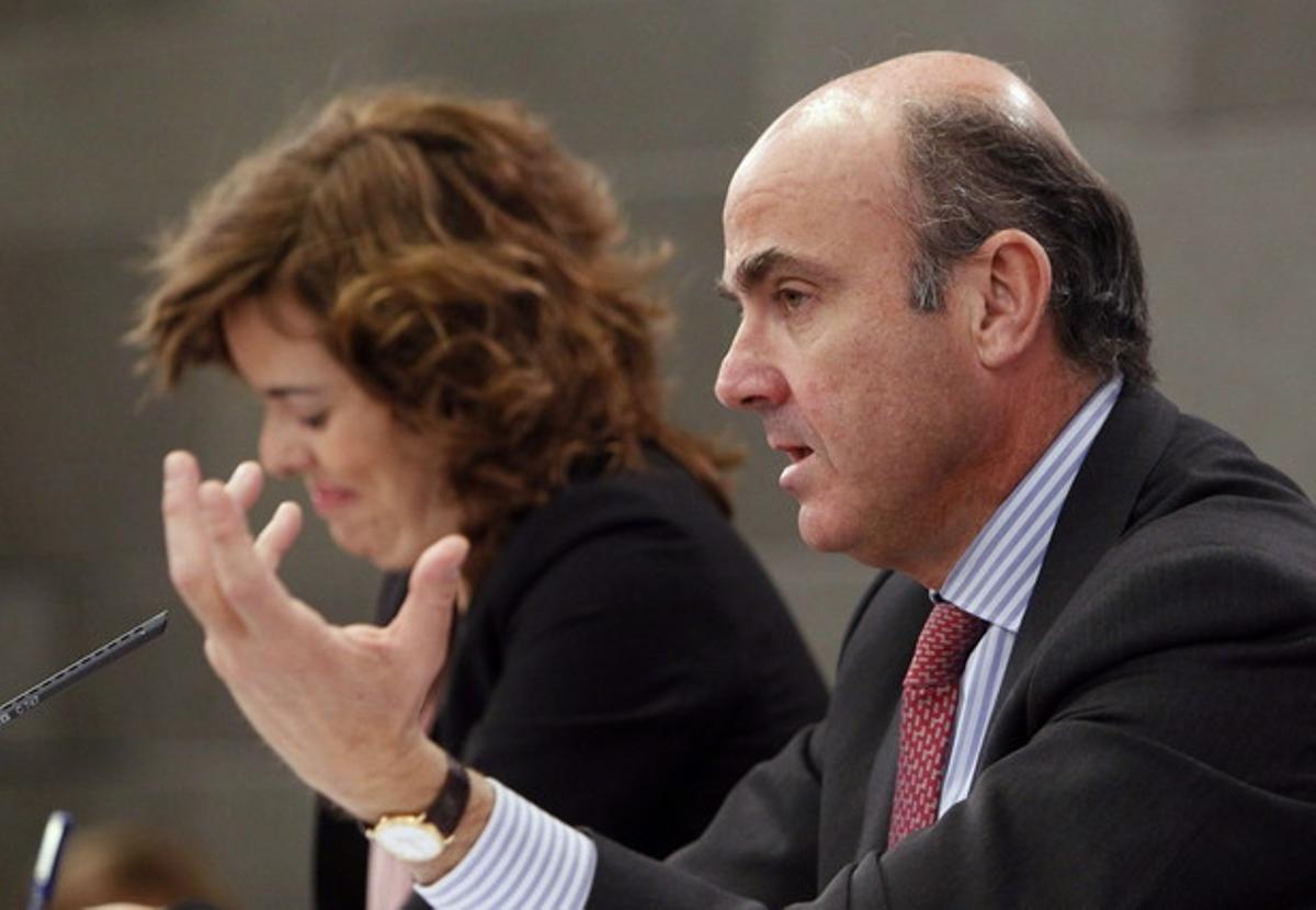 Luis de Guindos, con Soraya Saenz de Santamaría, tras el Consejo de Ministros.