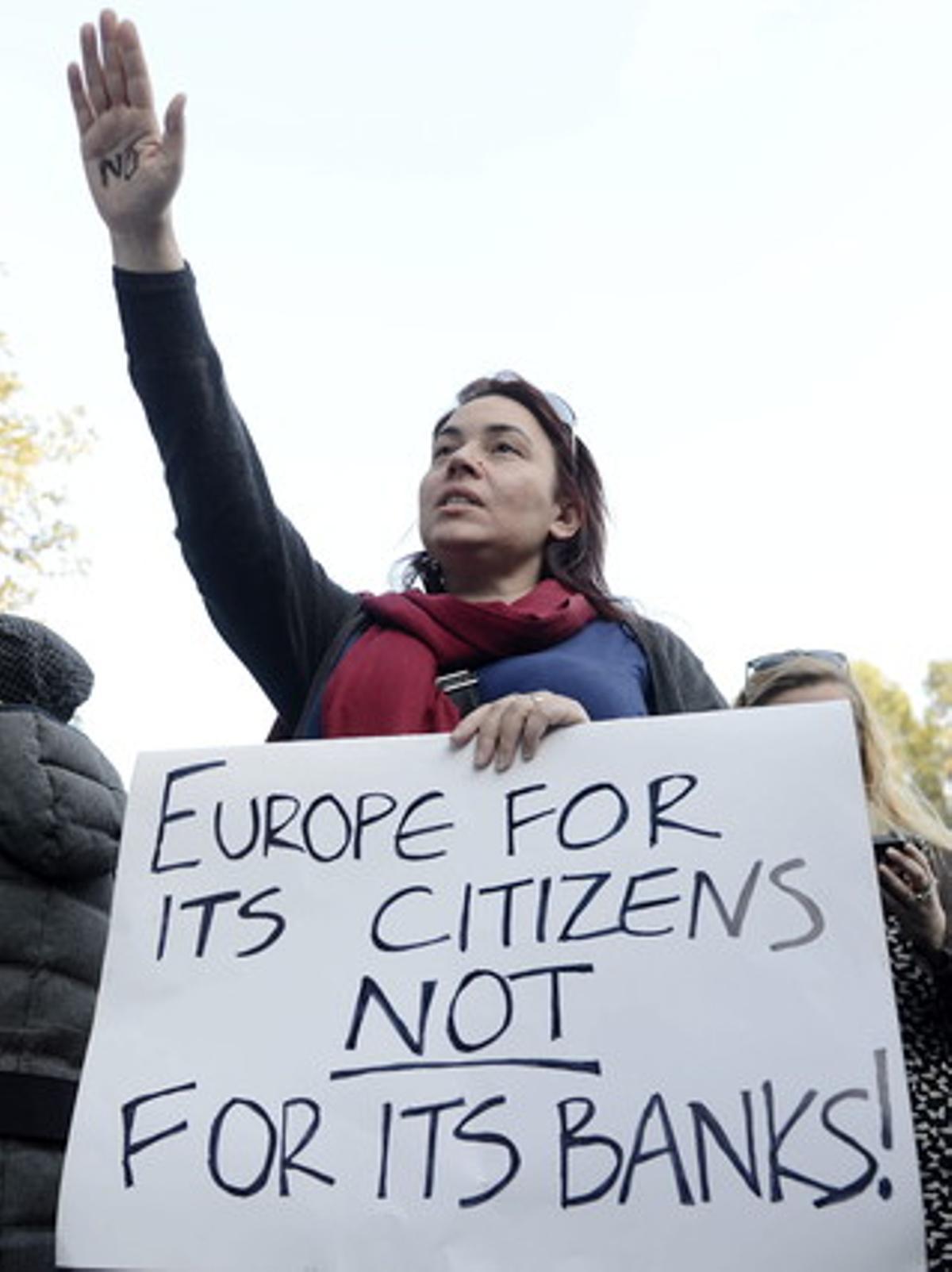 Una mujer protesta en Nicosia, este lunes, contra las medidas del Eurogrupo con un cartel en el que se lee Europa es de sus ciudadanos, no de sus bancos.