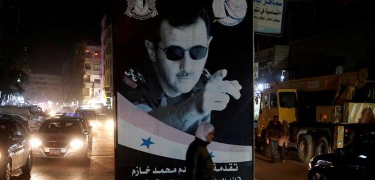Una mujer pasa ante un poster del presidente sirio, Bashar al-Assad, en Damasco.