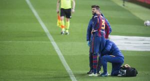Piqué es atendido por los doctores antes de volver a salir al partido contra el Sevilla.