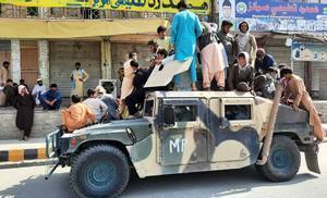 Un grupo de combatientes talibanes y residentes locales sube a un vehículo militar confiscado al ejército afgano en la provincia de Laghman.