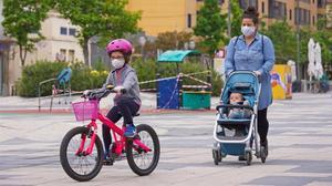 Madre pasea con su hija por Igualada, el primer dia que pueden salir los niños menores a la calle.