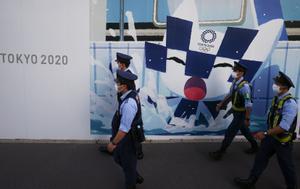 Policías japoneses pasan frente a un cartel que anuncia los Juegos Olímpicos de Tokio 2020 en la ciudad nipona de Hiroshima.