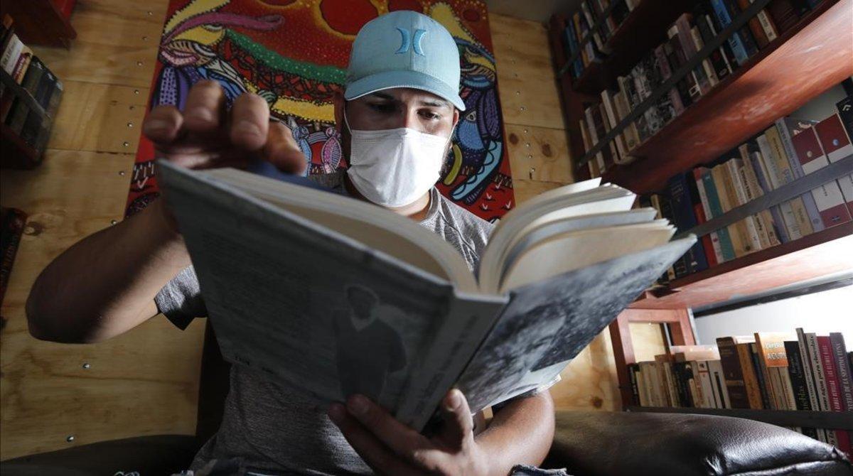 Un hombre lee en su domicilio.