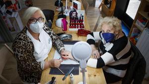 Angels Salvador en su centro de estética, atendiendo a una clienta de toda la vida y vecina del barrio, Teresa Doménech.