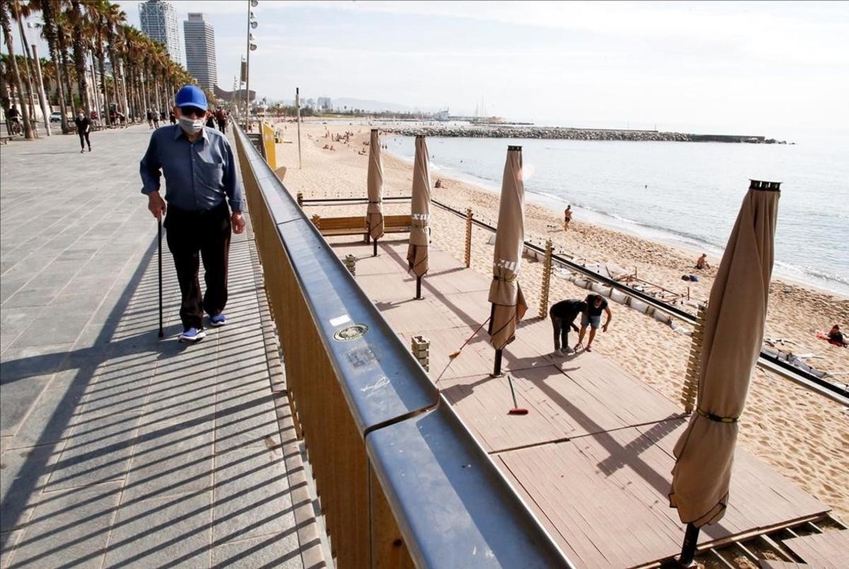 Trabajadores de un chiringuito de la Barceloneta preparan el local para su próxima apertura.