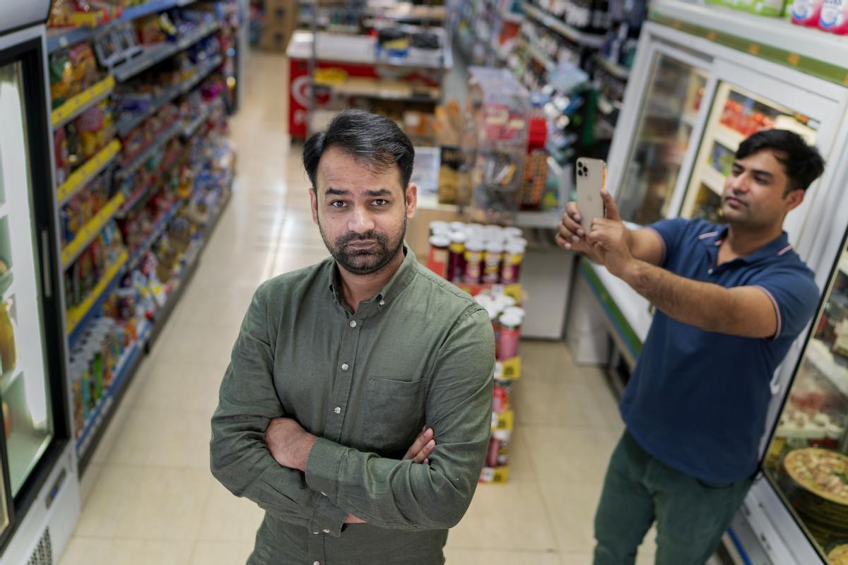 Rustem Iqbal posa en el Súper Pim Pam, en la calle Girona, junto a su hermano Qasim, su cámara de TikTok.