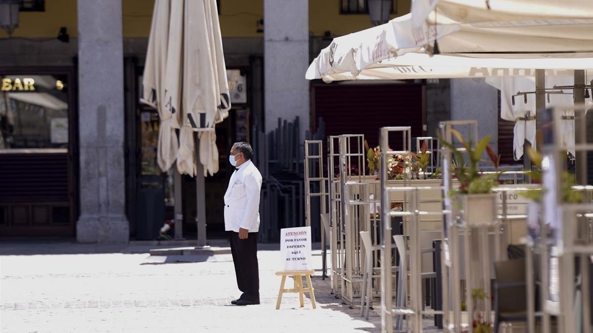 Un camarero espera clientes en un restaurante de la plaza Mayor.