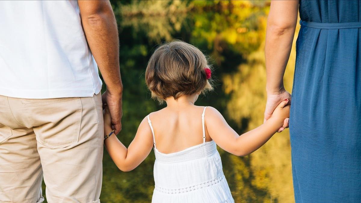 Una niña, en compañía de sus padres.