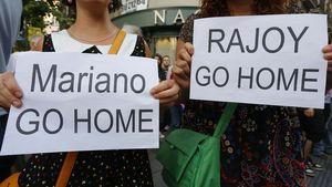 Dos manifestantes piden la dimisión de Rajoy frente a la sede del PP en Madrid este martes.