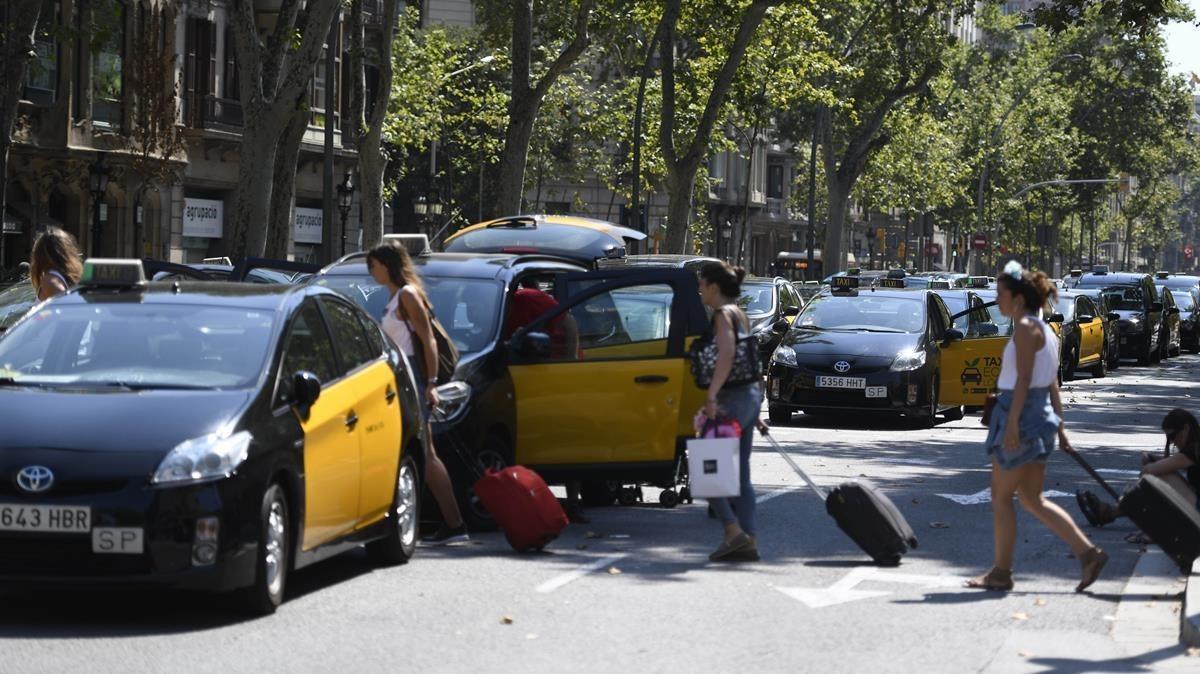 Turistas con maletas pasan entre los taxis parados.