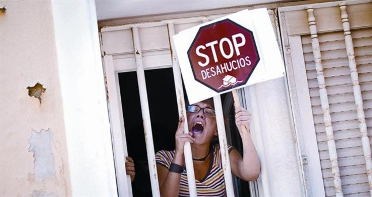 Una mujer protesta desde la ventana de una casa durante un acto de desahucio, en junio del 2011, en Madrid.