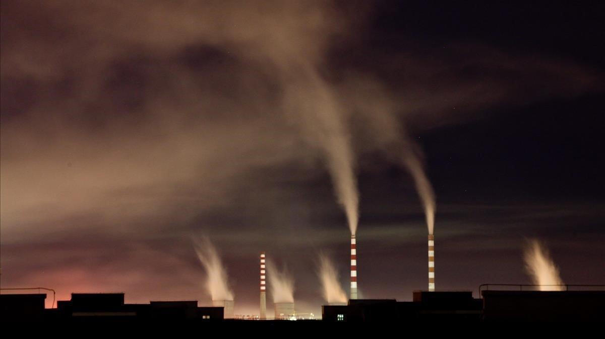 Chimeneas de una planta de energia de carbon emiten humo durante la noche en Changchun en China