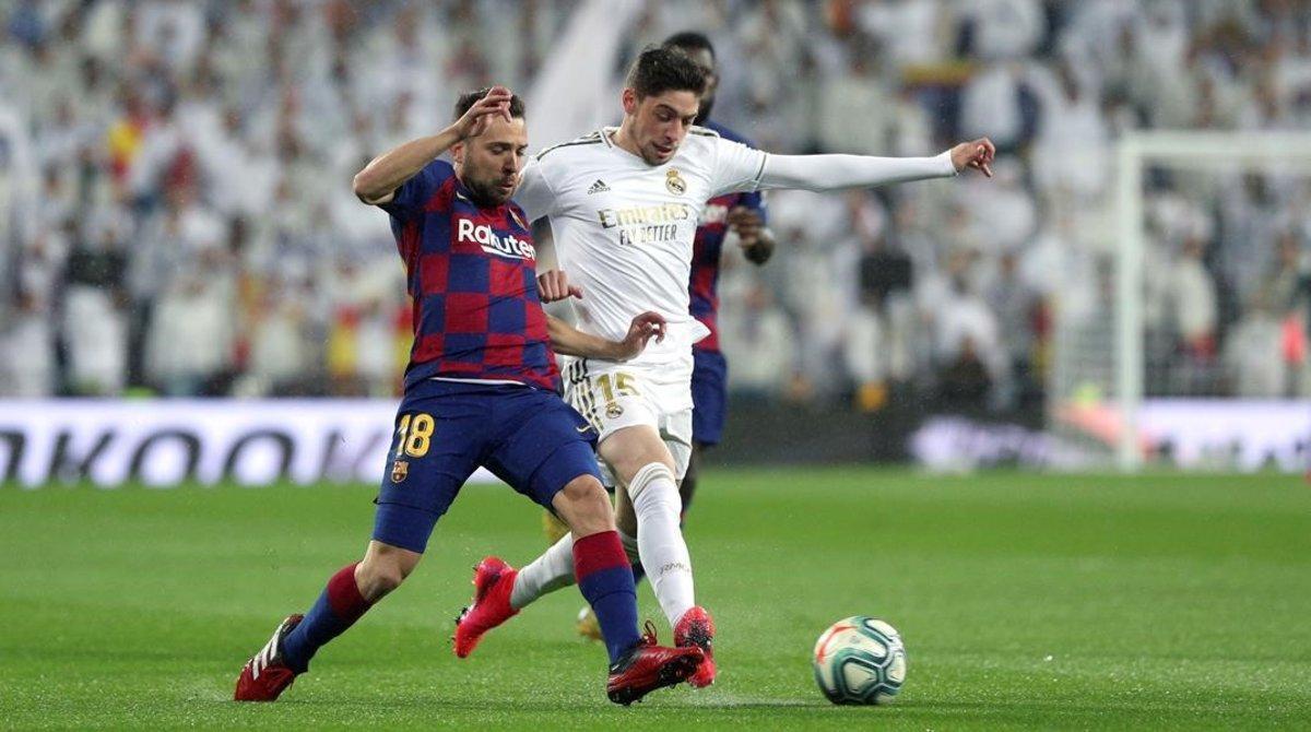 Valverde y Jordi Alba pugnan por un balón en el clásico.