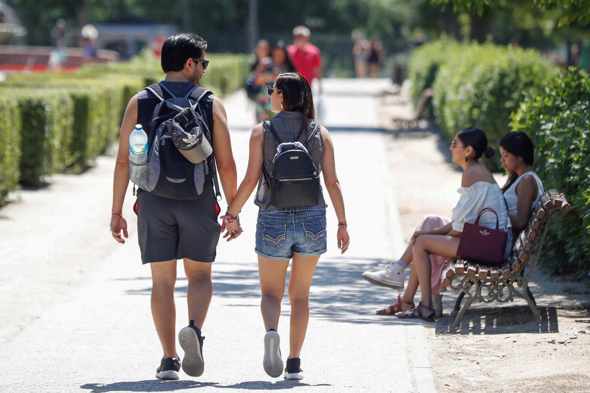 Dos jóvenes pasean por un parque de Madrid.