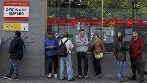 Parados en la entrada de una oficina de empleo de Madrid.
