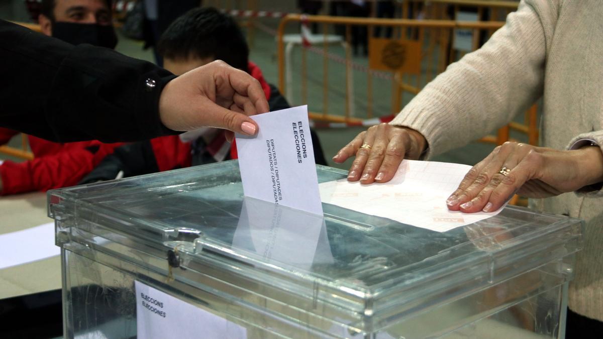 Una persona deposita el voto en la urna en las elecciones del 14-F