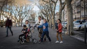 Una mujer camina con sus hijos por el centro de Béziers.