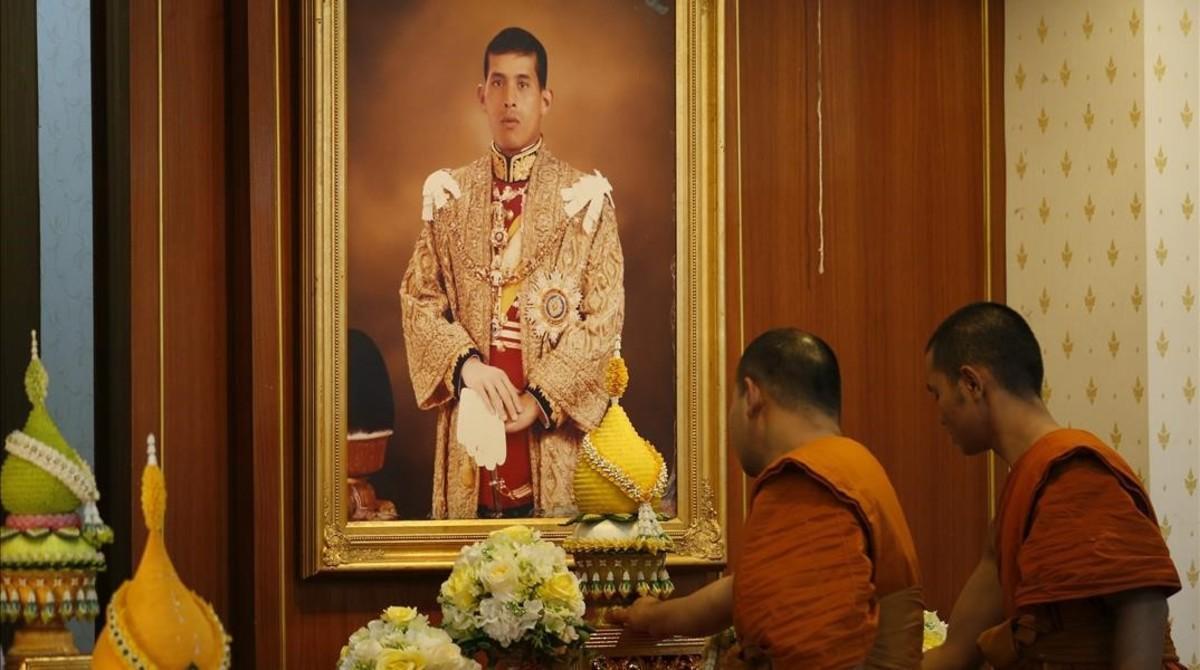 Monjes budistas se preparan para rezar ante un retrato del príncipe heredero de Tailandia, en el templo Wat Yannawa de Bangkok, este jueves.