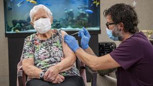Una anciana, de 90 años, recibe su primera dosis de la vacuna Pfizer-BioNTech.