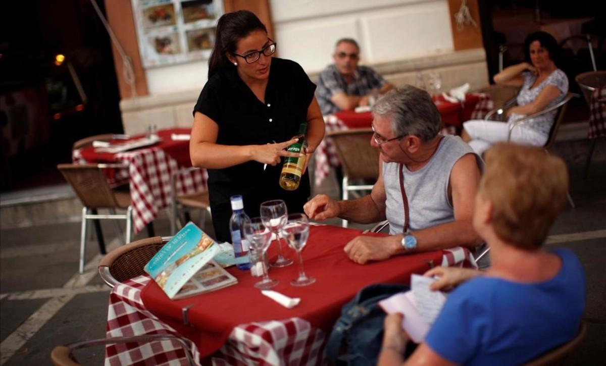 Una camarera con contratotemporal sirve vino a unos clientes en el Casino de Ronda.
