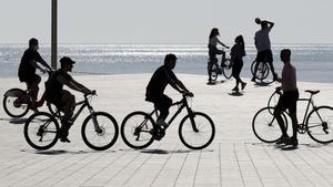 Gente con bicicletas en la playa de la Barceloneta.