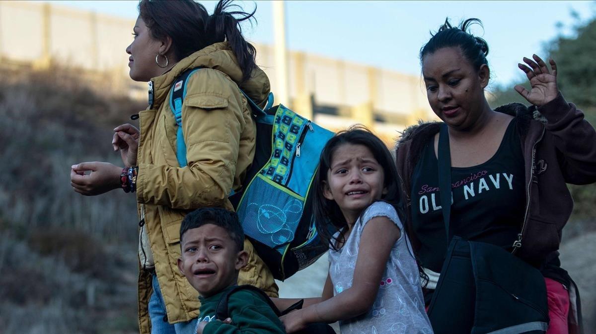 Dos mujeres y dos menores centroamericanos son detenidos por agentes de EEUU tras cruzar la frontera por Playas de Tijuana, en diciembre del 2018.
