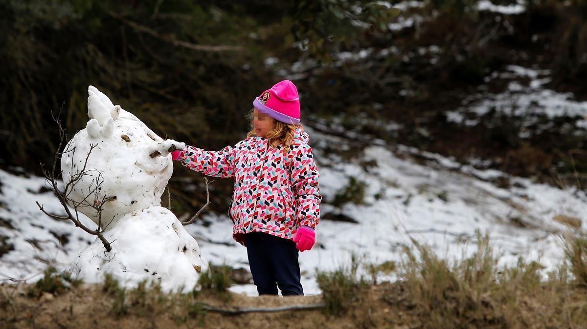 Una niña, con un muñeco de nieve en la localidad alicantina de Alcoy, este viernes.