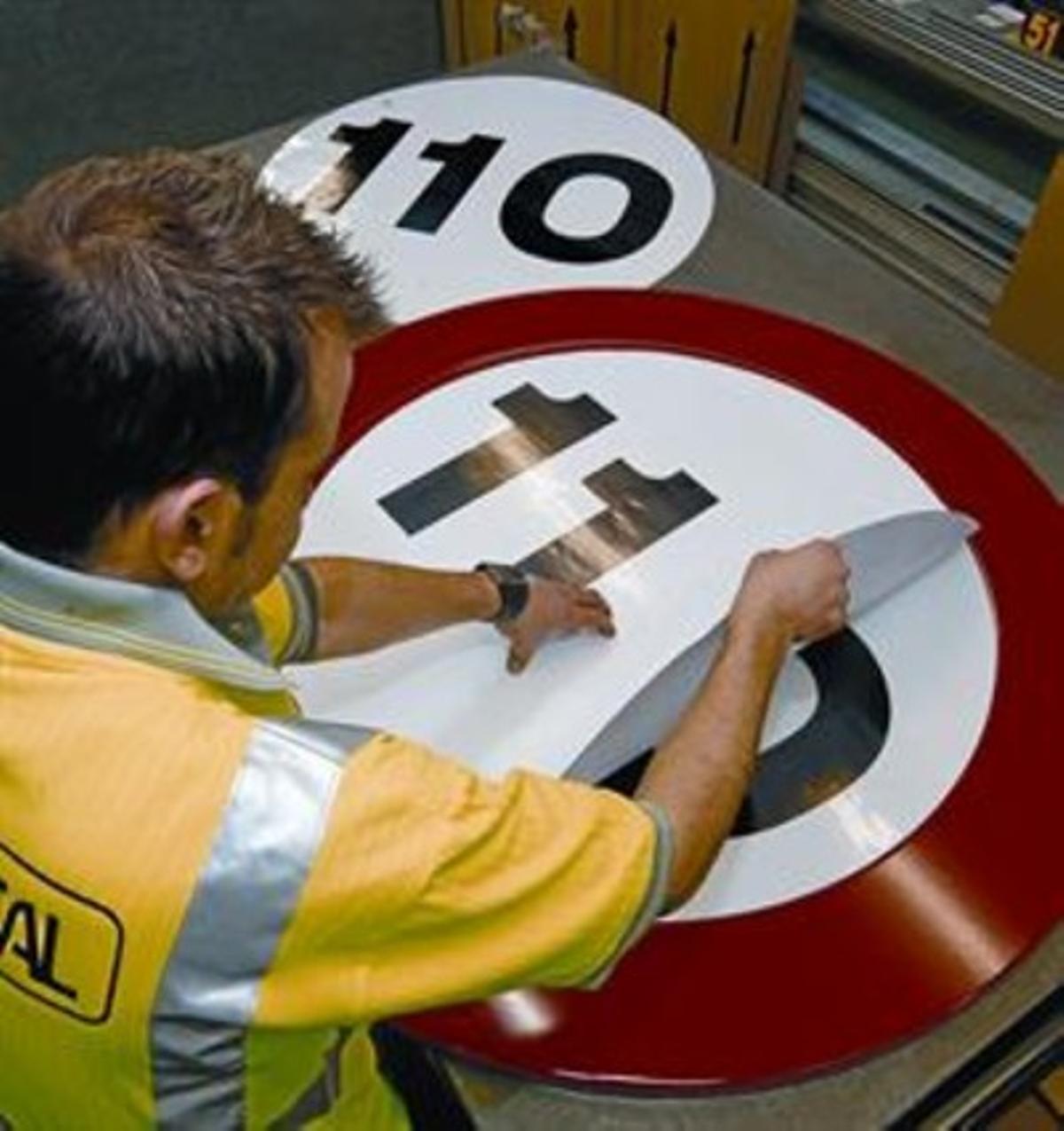 Un empleado de Proseñal pega el límite de velocidad que regirá a partir del lunes a una señal.