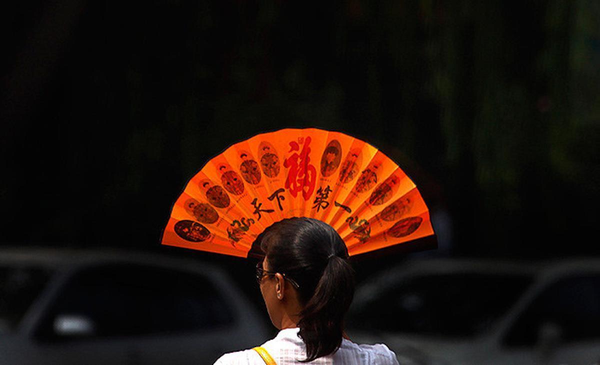 Una dona es tapa la cara amb un ventall per alleujar la calor en un carrer de Pequín.