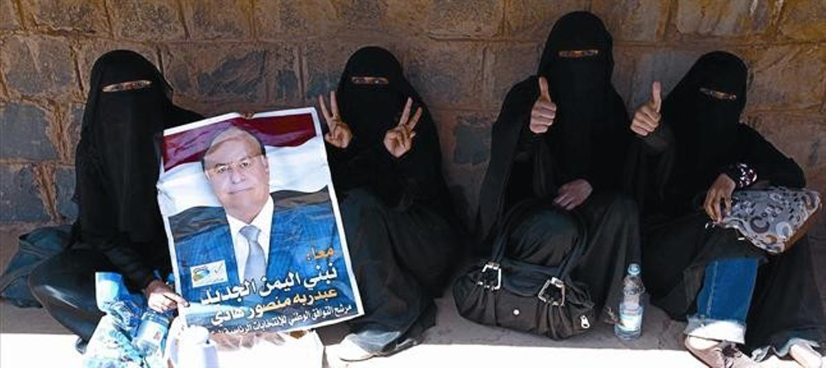 Mujeres yemenís con un cartel electoral del vicepresidente y candidato único Abdrabbo Mansur Hadi, en Saná, ayer.
