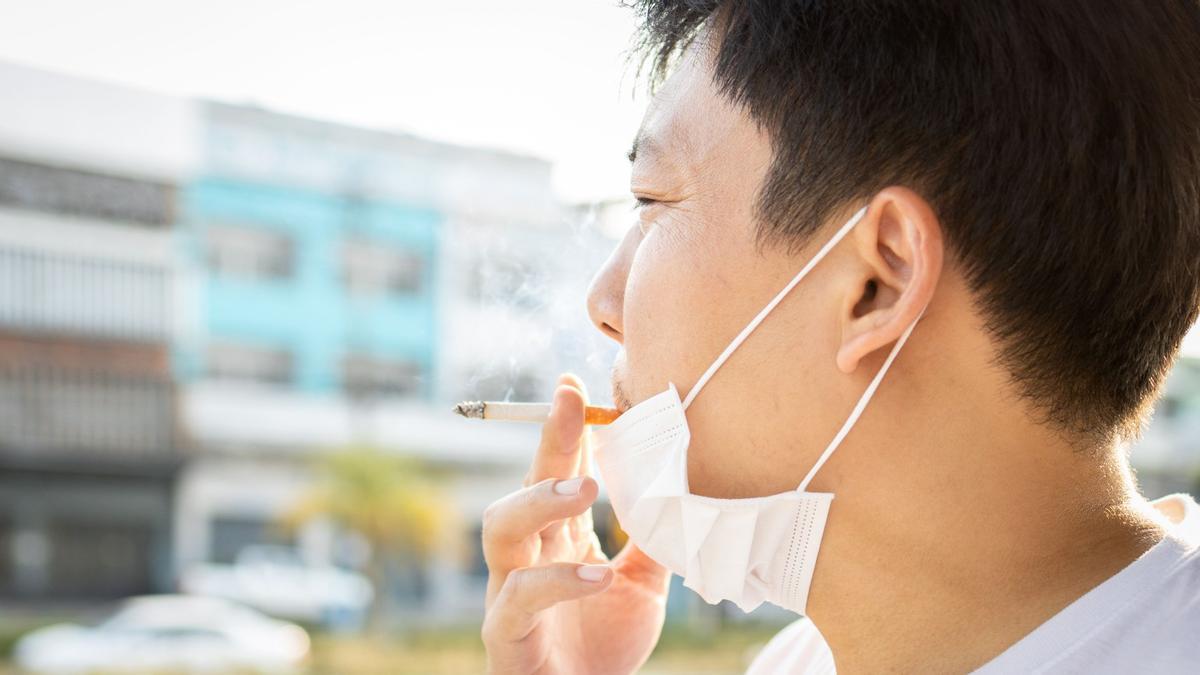 Un hombre con la mascarilla bajada para fumarse un cigarrillo.