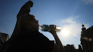 Un turista se refresca en Barcelona durante unaola de calor.