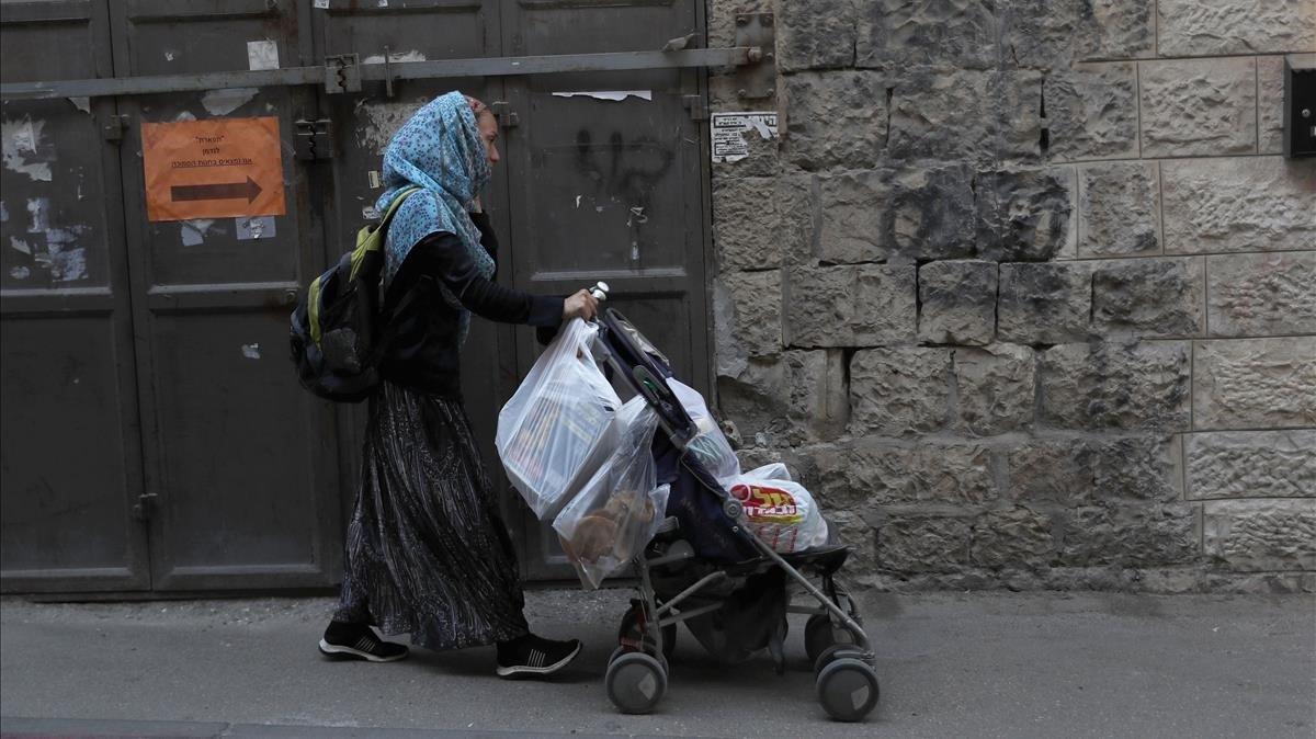 Una judía ultraortodoxa camina por Jerusalén con un carrito cargado con compras antes del nuevo confinamiento, este jueves.