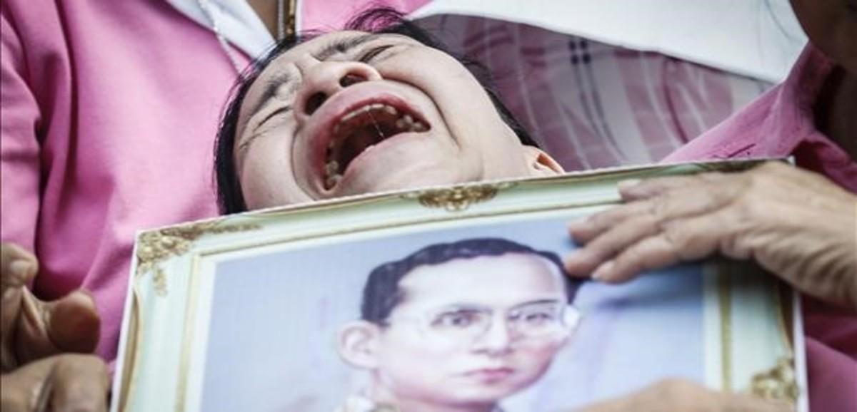 Una mujer llora a las puertas del hospital con la la foto del rey Bhumibol.