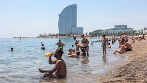 Soportando las altas temperaturas en la playa de la Barceloneta este mediodía