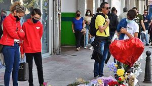 Varias personas, ante la ofrenda floral en recuerdo del joven Samuel Luiz.