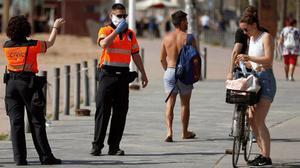Agentes cívicos de Barcelona informan a una joven de la obligatoriedad de llevar mascarilla.