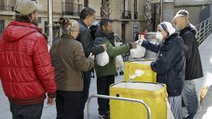 Voluntarios del Comedor Reina de la Paz de las Misioneras de la Caridad reparten alimentos entre personas necesitadas, en el barrio del Raval de Barcelona, el 12 de abril.