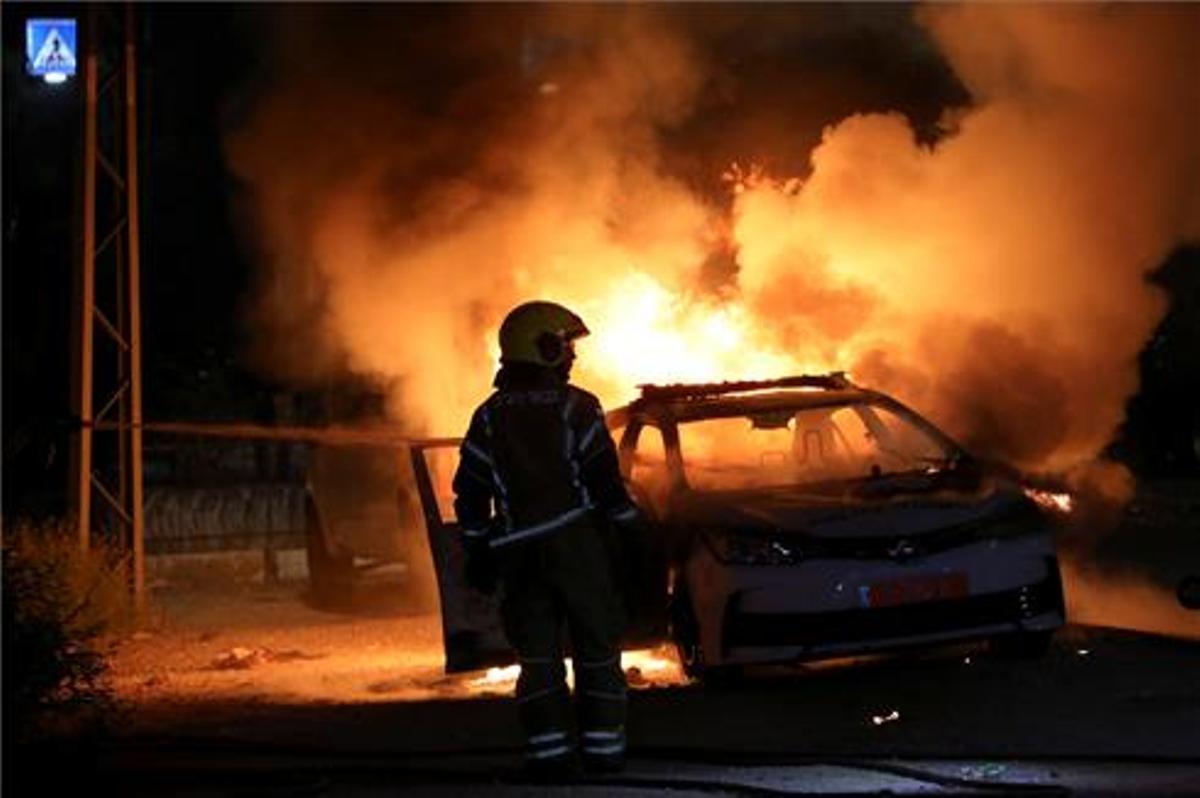 Un coche de la policía incendiado durante los choques en la ciudad de Lod.