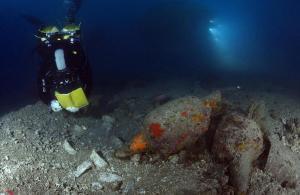 Un arqueólogo, junto a las ánforas que transportaba el barco romano que se ha localizado en las proximidades de las islas Formigues.