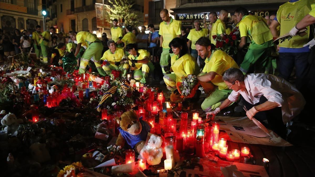 Trabajadores municipales recogen las ofrendas populares a las víctimas del atentado de la Rambla, en la noche de este lunes.