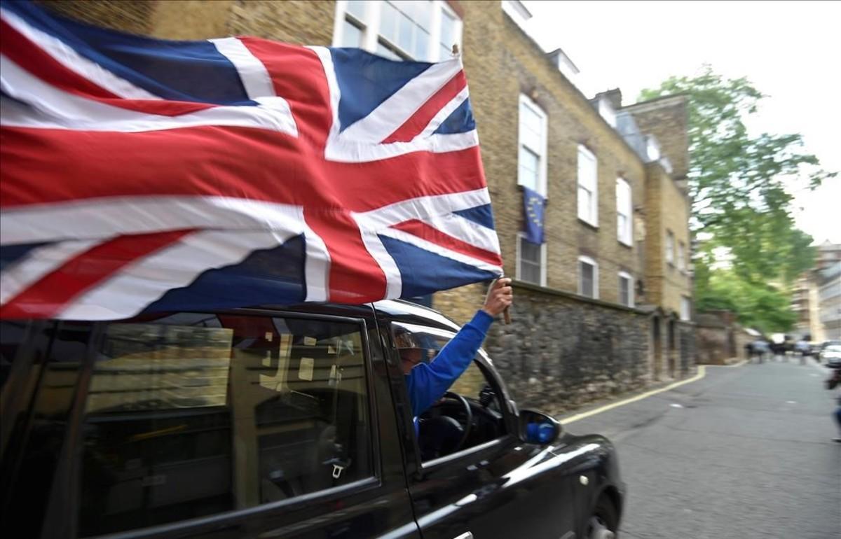 Un motorista con una bandera británica en el centro de Londres.
