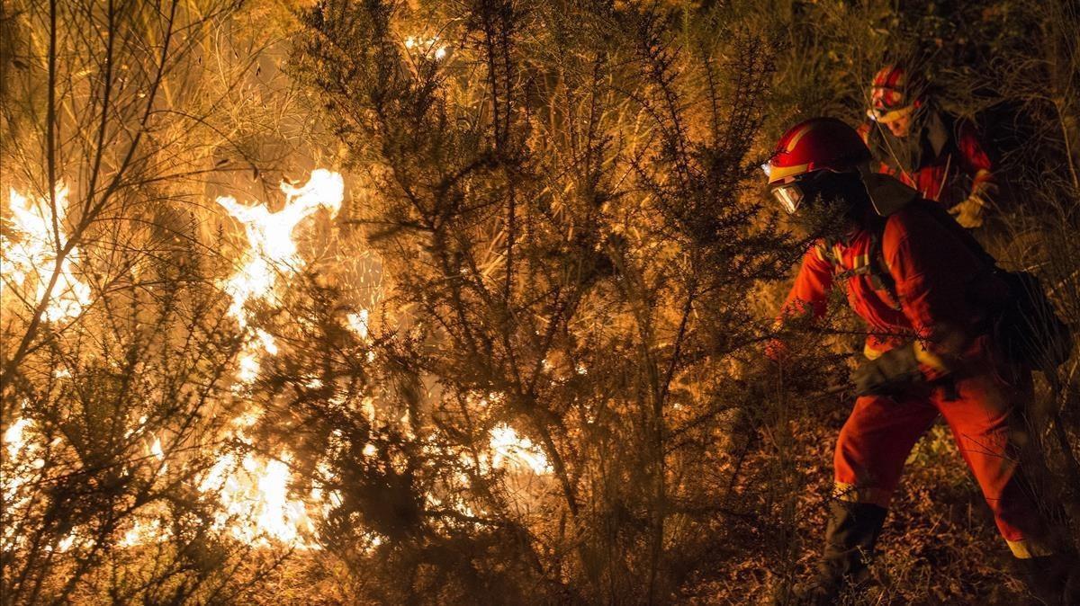 Unos bomberos luchan contra el fuego en Vilamarin, en Galicia.
