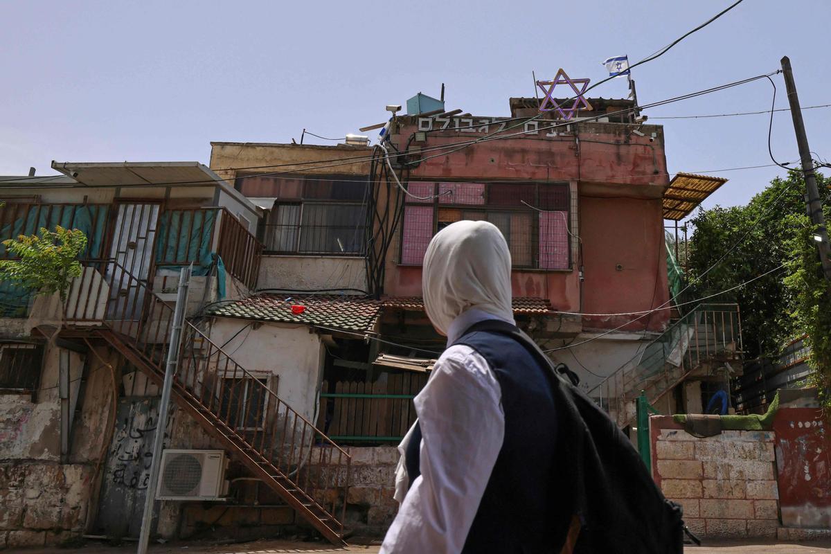 Una niña pasa por delante de una casa ocupada por israelís en el barrio de Sheik Jarrah.