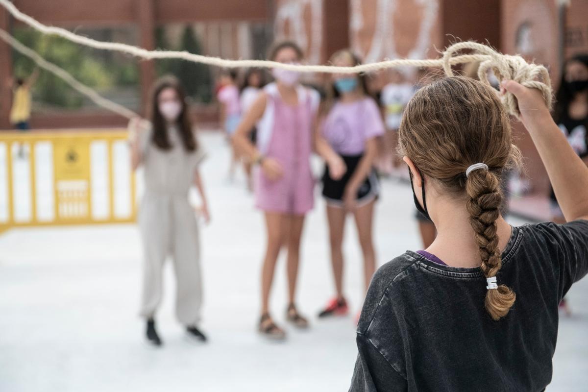 Niños y niñas con mascarilla juegan en el patio de una escuela de Esplugues