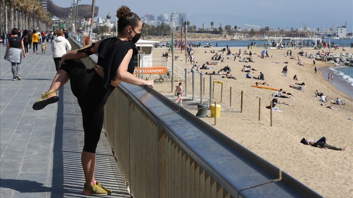 Sanidad propone mascarilla en la playa solo para pasear y si no hay distancia. En la foto, una chica hace deporte en el paseo Marítim cerca de la Barceloneta.