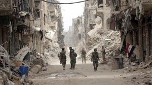 Soldados del Ejército de Damasco patrullan por el barrio deYarmouk, en el sur de la capital siria.